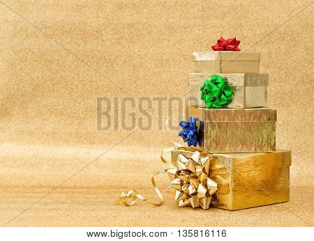 Gift boxes with multicolor ribbon bow on golden background. Holidays greetings card