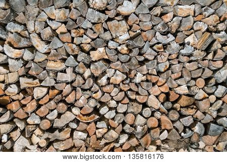 Stack of firewood consisting of many small logs in the sunshine in close-up