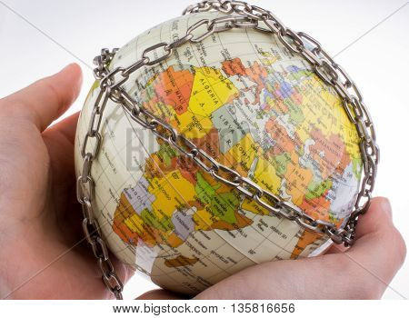 Hand holding a chained globe in chains