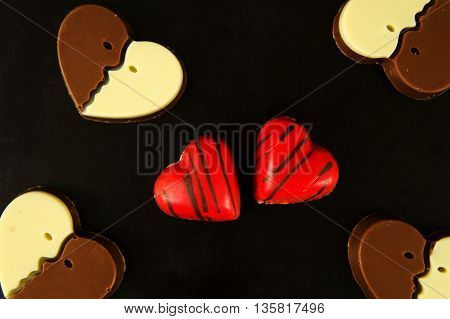 chocolate candies in a heart shape on black background
