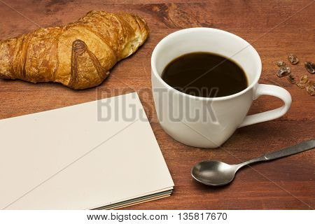 A photo of cup of dark coffee with some cane sugar a spoon a croissant and a blank notepad with copyspace on a dark wooden board texture