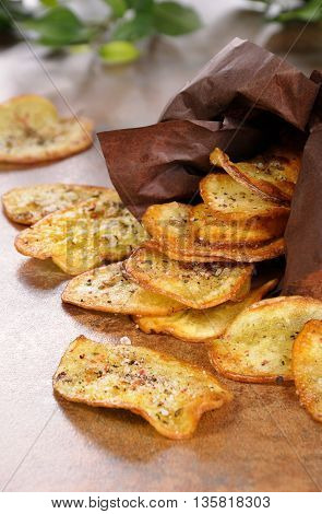 Fried potato chips scattered out of paper bags on the table