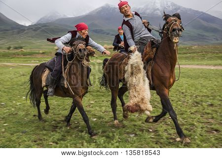 ISSYK KUL, KYRGYZSTAN - MAY 28, 2016: Nomad horse riders try to grab the goat carcass during the traditional horse games of Ulak Tartysh, known also as Buzkashi.