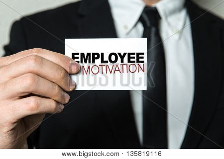 Business man holding a card with the text: Employee Motivation