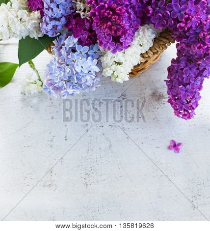 Bunch of fresh lilac flowers in basket close up with copy space on table