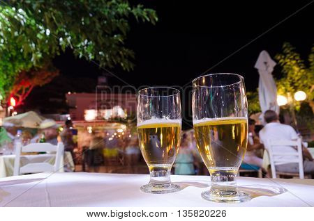 Two glasses of beer on a table.