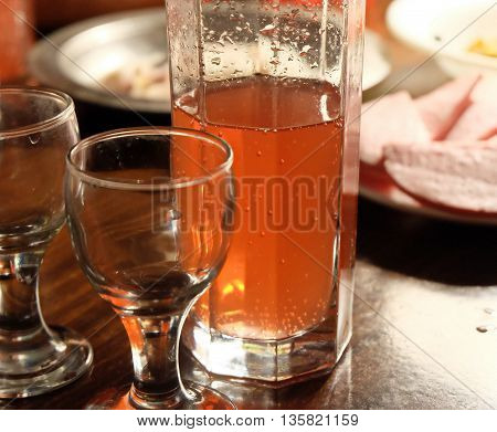 Half glass of ale standing on a rustic wooden table with small empty vodka glasses.