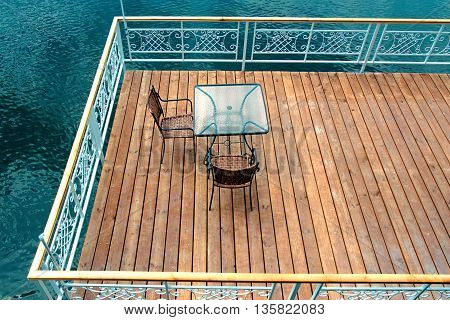 A table and chairs on a dock near the lake