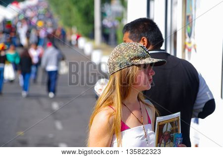 QUITO, ECUADOR - JULY 7, 2015: Unidentified girl selling a little poster of pope Francsico before entering to mass, visit on Ecuador.