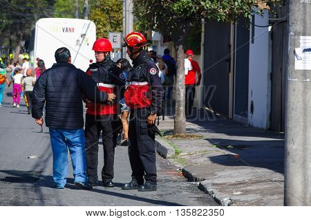 QUITO, ECUADOR - JULY 7, 2015: A man speaking with two firefighters on the street, people entering to pope Francisco mass.