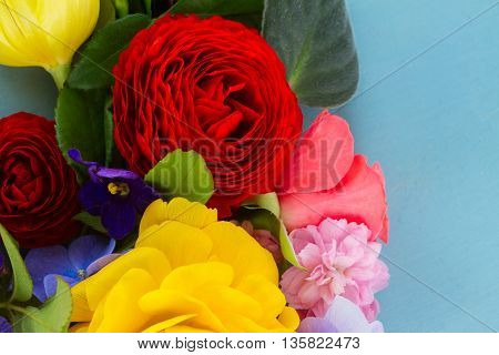 Fresh cut Flowers Background on Blue - ranunculus, pansies, roses
