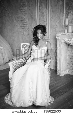 Beautiful bride with perfect makeup and hairstyle sitting in armchair