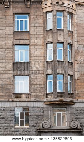 Several windows in a row and bay window on facade of urban office building front view St. Petersburg Russia