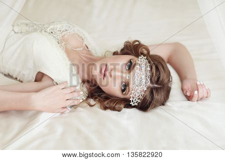 Studio Portrait Of Beautiful Bride With Perfect Hairstyle And Makeup Lying On The Bed.