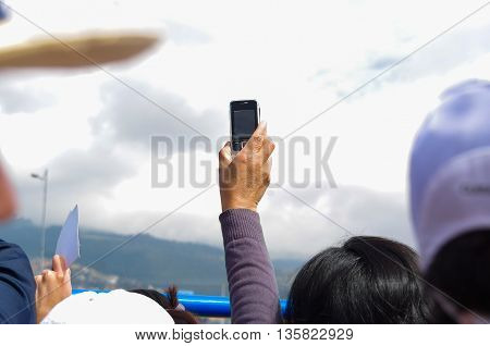 QUITO, ECUADOR - JULY 7, 2015: A woman hand holding a mobile phone on her hand, trying to film pope Francisco, mass event.