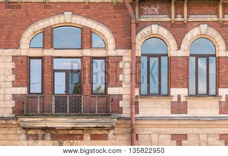 Three windows in a row and balcony on facade of urban apartment building front view St. Petersburg Russia
