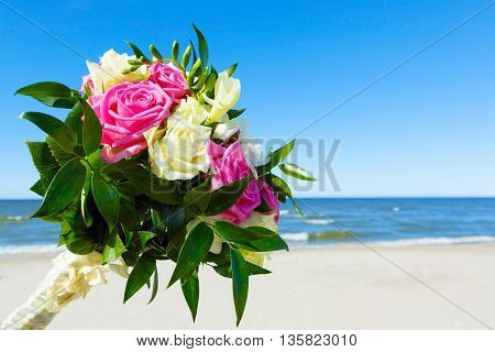 Wedding bouquet on a background of sky and sea
