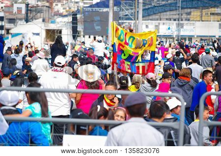QUITO, ECUADOR - JULY 7, 2015: In the middle of thousand people, colored flag with the words, Colombia is present here.