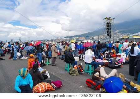 QUITO, ECUADOR - JULY 7, 2015: People sitting and lying on the floor, pope Francisco mass. Strong sun, various umbrellas.