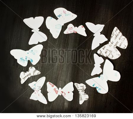 A photo of many white butterflies cut out of paper with calligraphic texts and watercolor stains forming a circle on a dark wooden background texture shot from above with copyspace