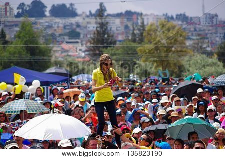 QUITO, ECUADOR - JULY 7, 2015: Just for a photo a woman is satnding up on a men shoulders, mobile phone camera on her hands.