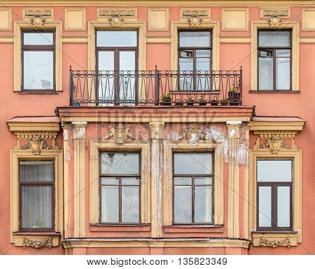 Several windows in a row and balcony on facade of urban apartment building front view St. Petersburg Russia