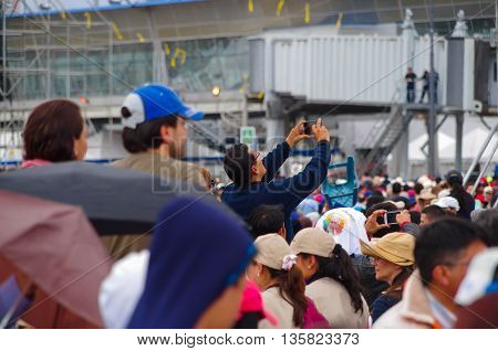 QUITO, ECUADOR - JULY 7, 2015: In the middle of a huge group of people, a man taking photos with his mobile phone. People around.