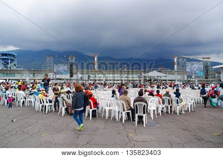QUITO, ECUADOR - JULY 7, 2015: Lots of people sitting on white chairs waitting for pope Francisco mass. Firts time for him in Ecuador.