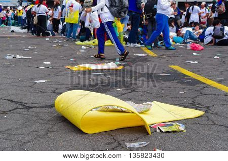 QUITO, ECUADOR - JULY 7, 2015: Yellow cardboard in the street, lots of garbage after an event, peple behind trying to get out.