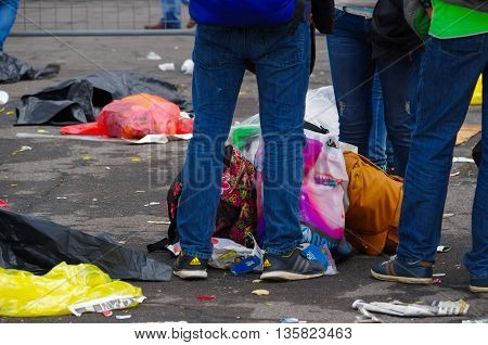 QUITO, ECUADOR - JULY 7, 2015: Mens legs guarding some bags on the floor, behind trash and garbage.