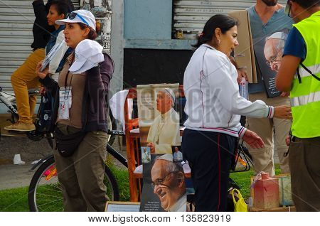 QUITO, ECUADOR - JULY 7, 2015: Unidentified womans selling pope Francisco posters outside of the mass, tshirts and hats.