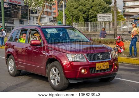 QUITO, ECUADOR - JULY 7, 2015: Police inside a wine color car, Suzuki big vitara. People outside,