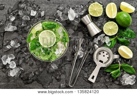 Cocktail with lime mint and ice. Bar drink accessories on black table background. Alcoholic and nonalcoholic cold drinks. Selective focus