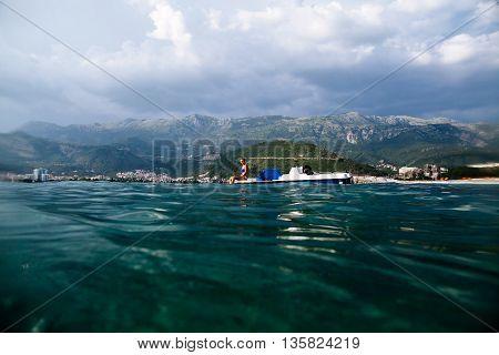 Girl Sunbathe In Sea On Paddle Boat Catamaran