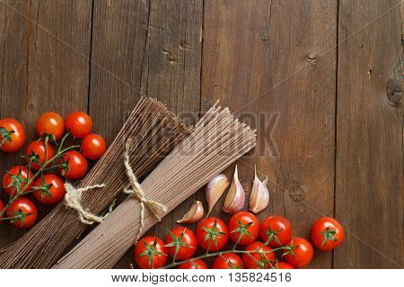 Two types of spaghetti tomatoes and garlic on wood