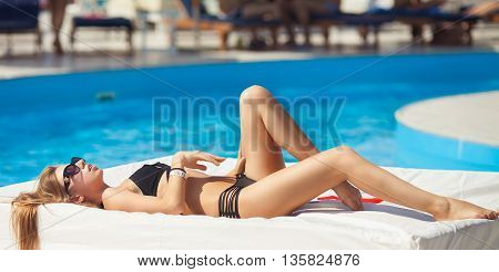 Portrait of a beautiful woman getting out of a swimming pool. beautiful long hair tanned female model posing by blue pool water. Outdoor summer portrait of sexy girl in sunglasses