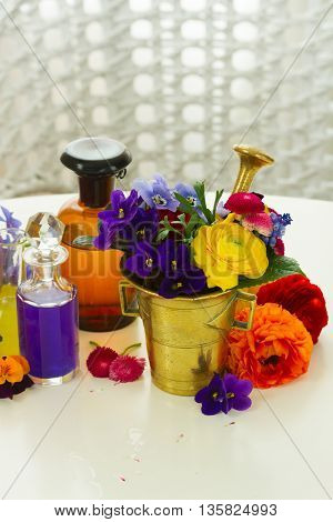 Flowers, mortar and bottles of potions on table, herbal medicine