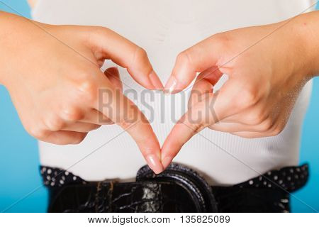 Love hope and charity concept. Woman hands creating heart sign symbol on blue background. Studio shot.