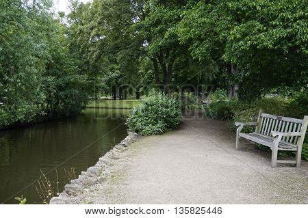 A wooden bench in the park on the river bank