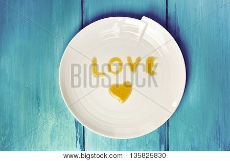 The word 'Love' written with honey on a white plate shot from above on a vibrant blue background texture with copyspace
