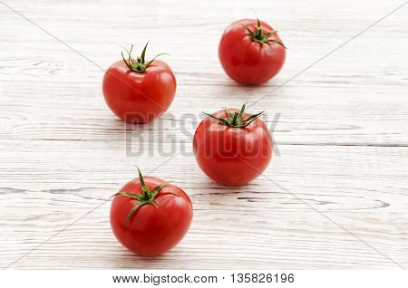 Red tomatoes on white wooden background. Copy space composition.