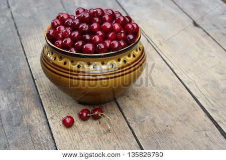 Sweet cherries in a clay bowl on wooden boards