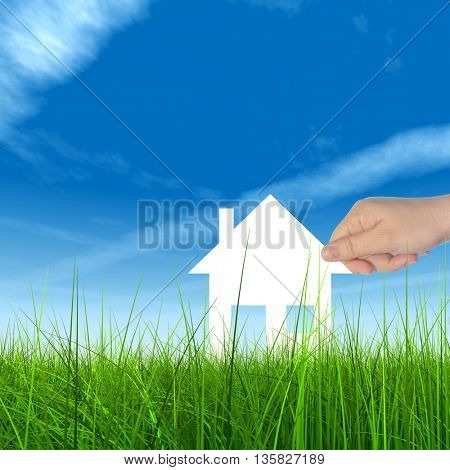 Concept or conceptual white paper house held in hand by a man in a green summer grass over a blue sky background with clouds
