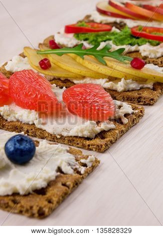 Bruschetta with ricotta and fresh berries fruits and vegetables.