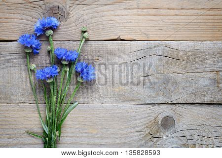 Bouquet of blue cornflowers on wooden background