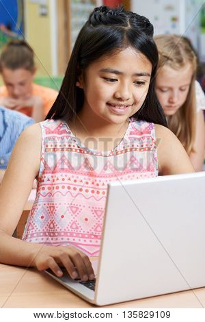 Female Elementary School Pupil Using Laptop In Computer Class