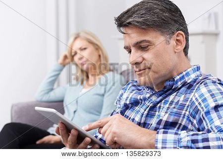 Unhappy Woman Sitting On Sofa As Partner Uses Digital Tablet