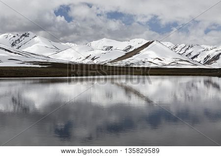 Reflections in the water of snow capped mountains and clouds.