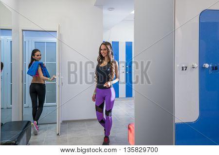 Charming girls pose in locker room of sports center
