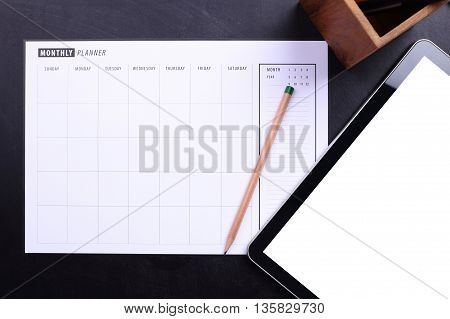 Planner schedule with pencil and blank screen tablet on black wooden
